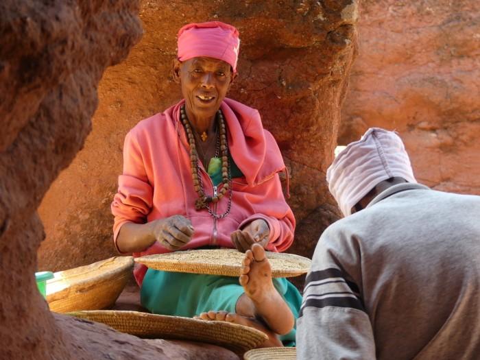 Anciana seleccionando el trigo en las proximidades de la iglesia
